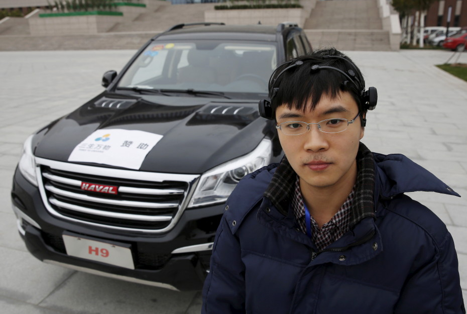 Researcher Zhang Zhao wearing a brain signal-reading equipment poses with a vehicle which can be controlled with his brain wave, during a demonstration at Nankai University in Tianjin, China, November 17, 2015. REUTERS/Kim Kyung