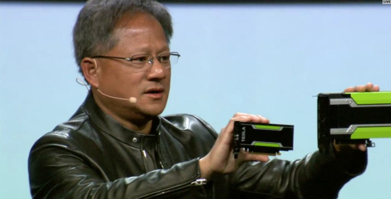 Jen-Hsun Huang of Nvidia shows off the company's Tesla M4 and Tesla M40 deep learning chips.