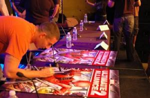 Daniel Dilallo signs a poster for a video game he worked on.