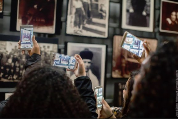 Kids can use smartphones for AR app at Holocaust Museum.