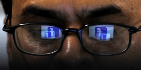 Facebook logo is reflected in glasses in this picture illustration