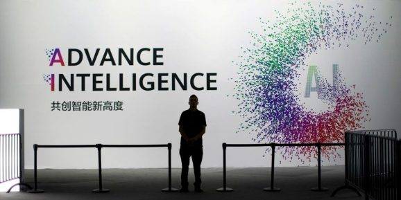 A security officer keeps watch in front of an AI (Artificial Intelligence) sign at the annual Huawei Connect event in Shanghai, China.