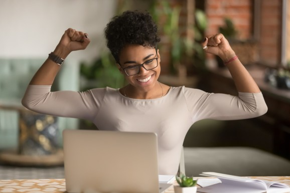 Excited happy african american woman feeling winner rejoicing online win got new job opportunity, overjoyed motivated mixed race girl student receive good test results on laptop celebrating admission
