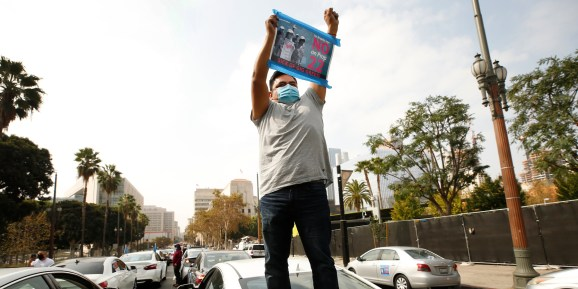 Rideshare driver Jesus Ibarra stands on his car in support as app based gig workers held a driving demonstration with 60-70 vehicles blocking Spring Street in front of Los Angeles City Hall urging voters to vote no on Proposition 22. Photo taken Oct. 8, 2020 in Los Angeles, Calif.