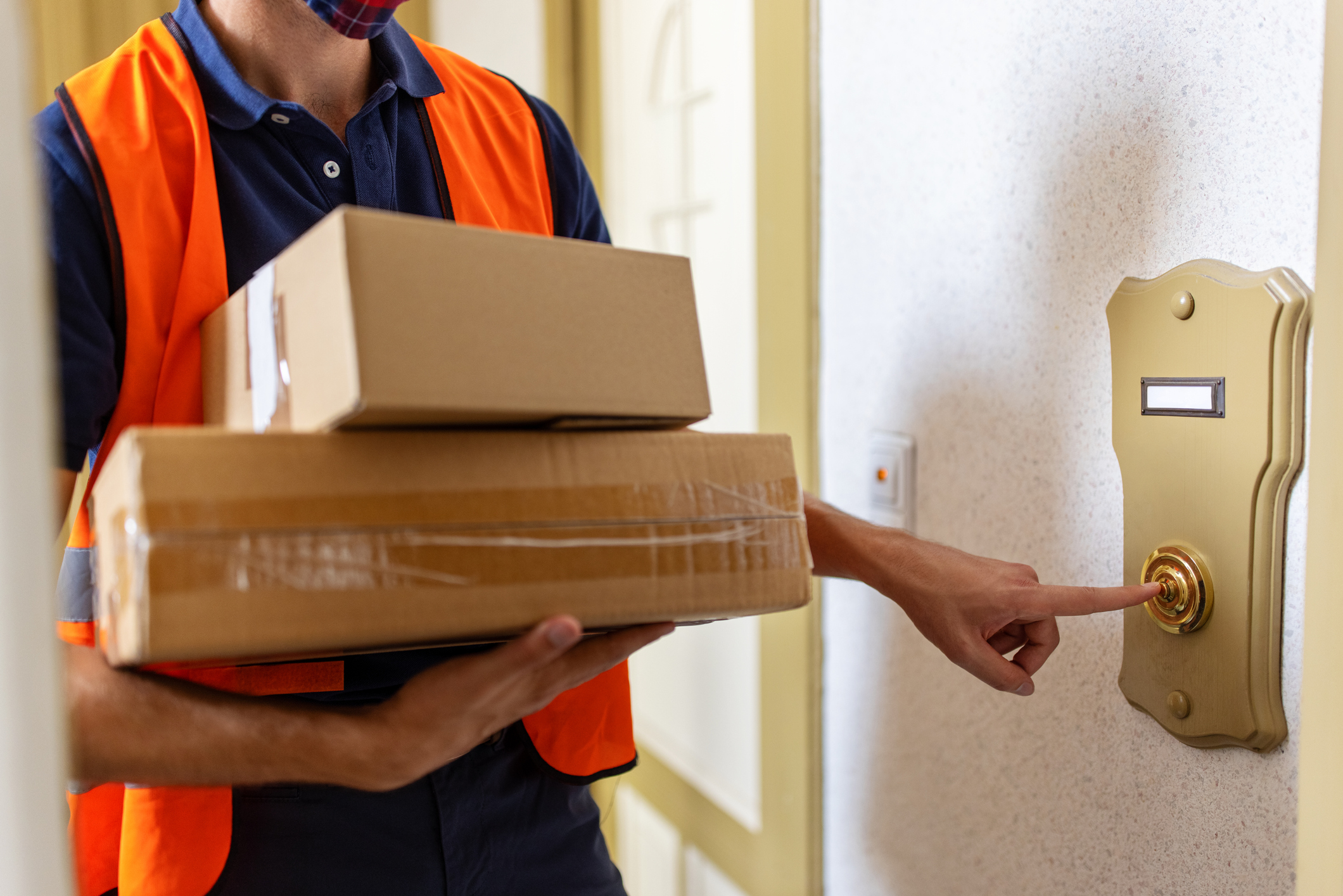 Cropped shot of a male courier delivery person holding parcel boxes and ringing doorbell. Postal worker doing a home delivery of parcel.