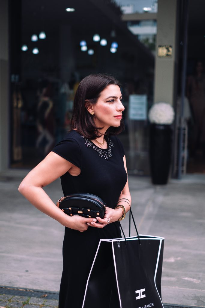 woman dressed with a litle black dress with a black bag in her hands