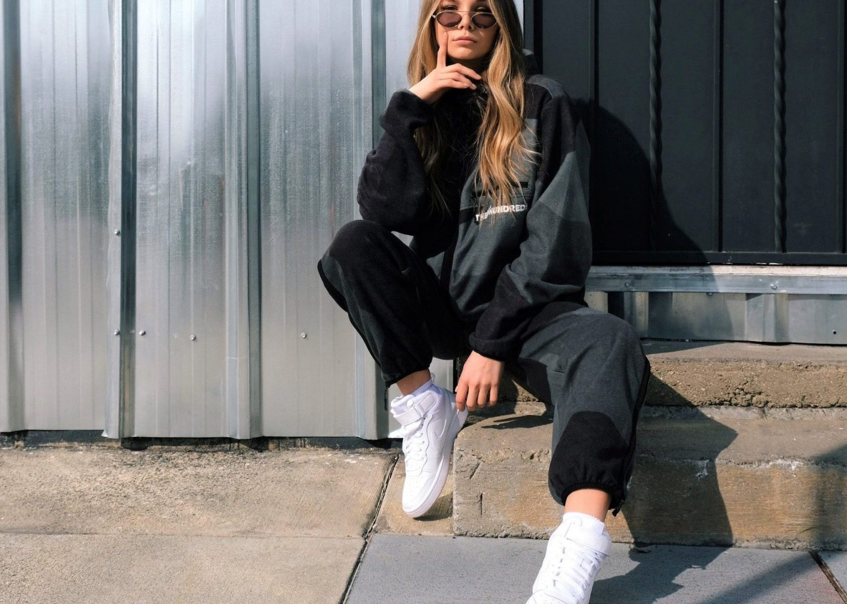 girl blonde with çong hair in all black sport jumpsuit and white sneakers seated in a walkside
