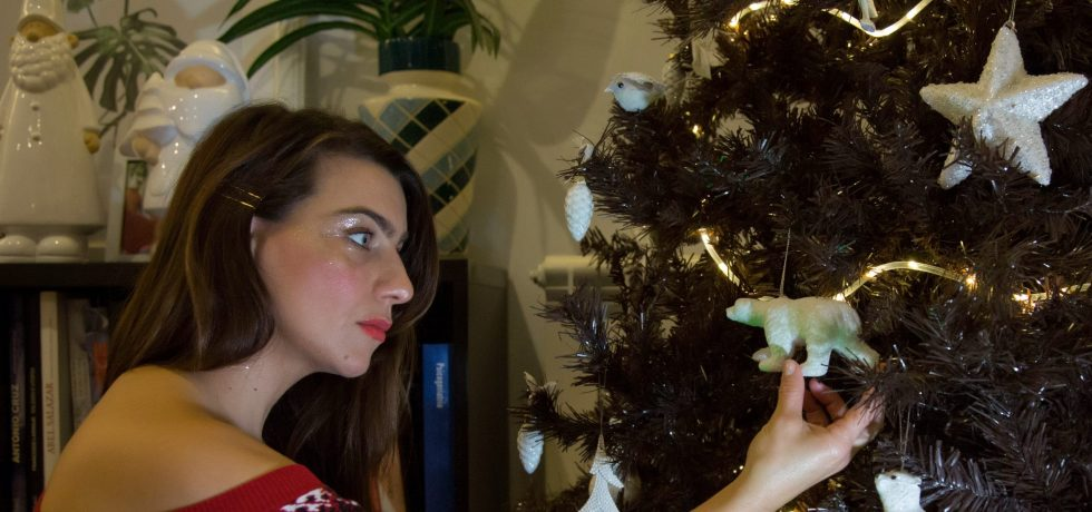 Vera Gallardo a fashion and beauty blogger advocating for sustainability, here dressed in a red sweater with sequins and christmas makeup red lips red blush soft in skin. Standing by the christmas tree holding a piece of decor .