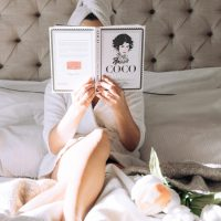 vera gallardo, fashion and beauty blogguer, layed on the bed, wearing a white rope and a white towel in her head. feat are showing the sunlights entering the room and crossing the bed, while she is reading a book from coco chanel, that hides her face.