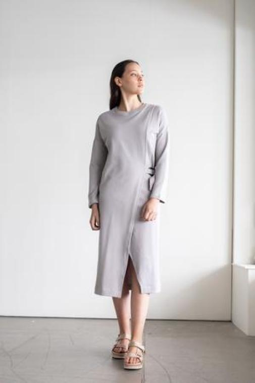 RECREATE sustainable brand woman wearing the dree in grey color wearing also sandals standing up at the window wearing her hair back and smooth makeup