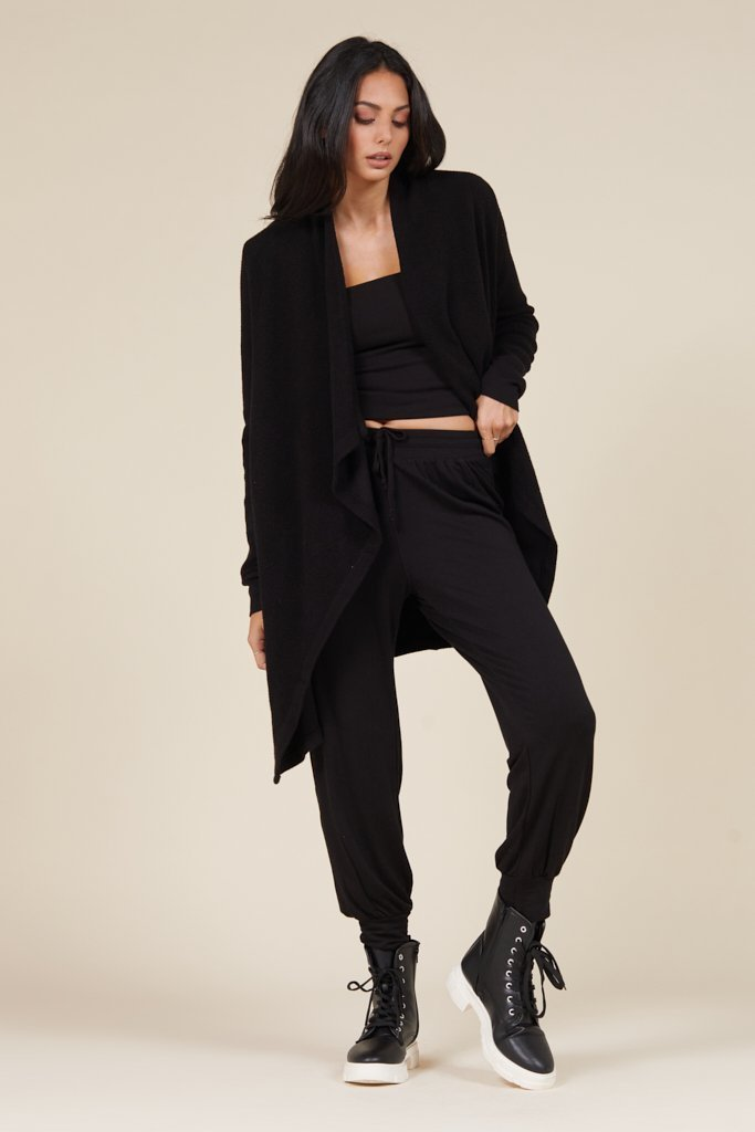 LAMADE CLOTHING BRAND loungwear girl wearing a total black set with  joggers top and cardigan and sneakers also black