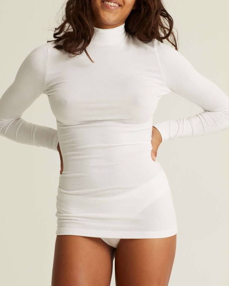 WORONSTORE sustainbale brand woman wearing their high neck sleek top in white color and white pantys
