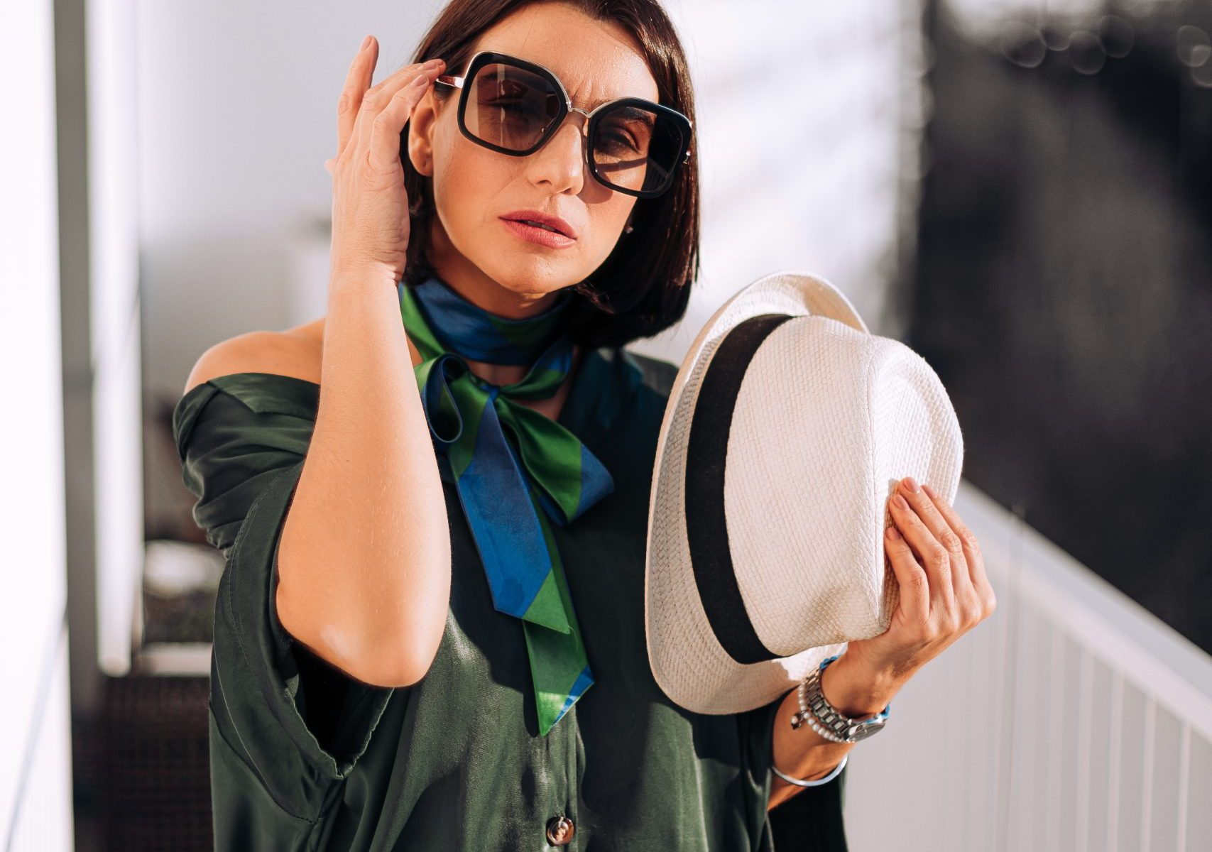 Vera Gallardo the sustainable fashion and beauty blogger wearing green scarf black glasses and with a hat in her left hand