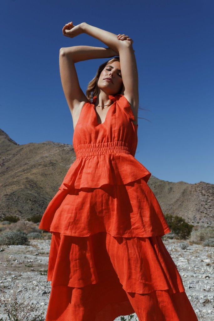 milo+nicki sustainable brand  the girl is wearing a long orangedress