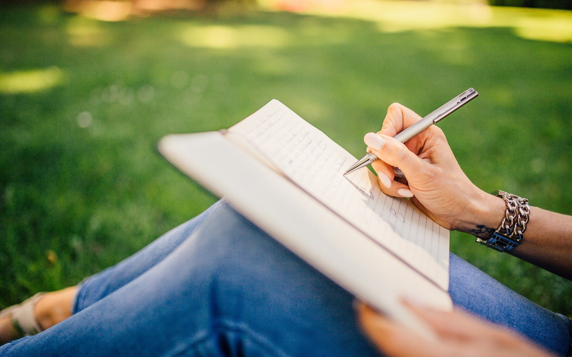 Girl writing with a pen and paper just showing her knees wearing blue jeans