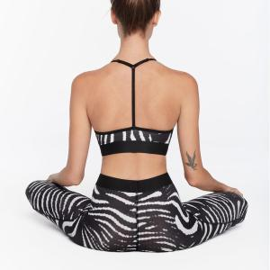 Girl standing sit legs crossed showing her backs wearing a VYAYAMA - DUSK PRINT CROP TOP