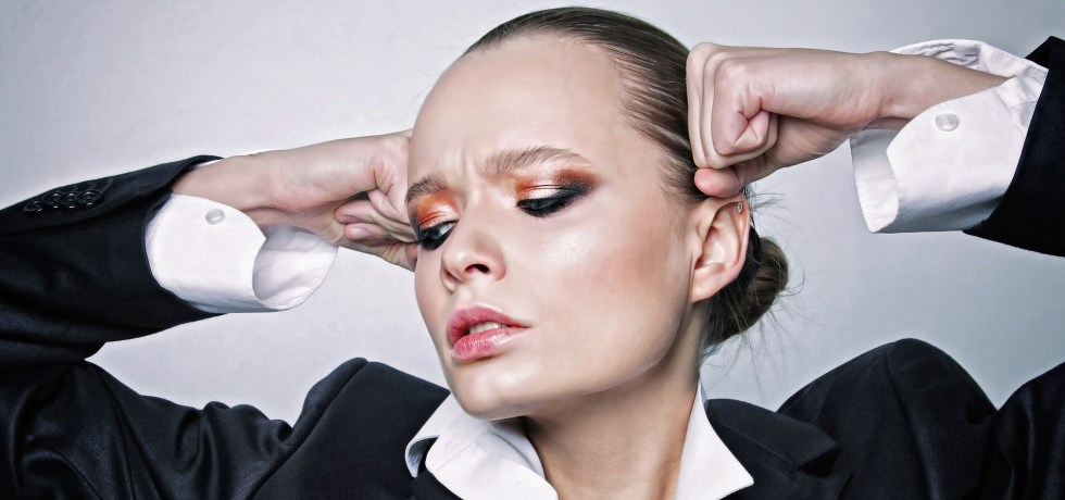 woman wearing gold orange eyeshadow and with her hair totally pulled up in the back wearing black blazer and white shirt