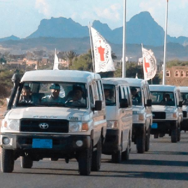 Caravana de vehículos 4x4 en la carretera mostrando banderas de ayuda humanitaria