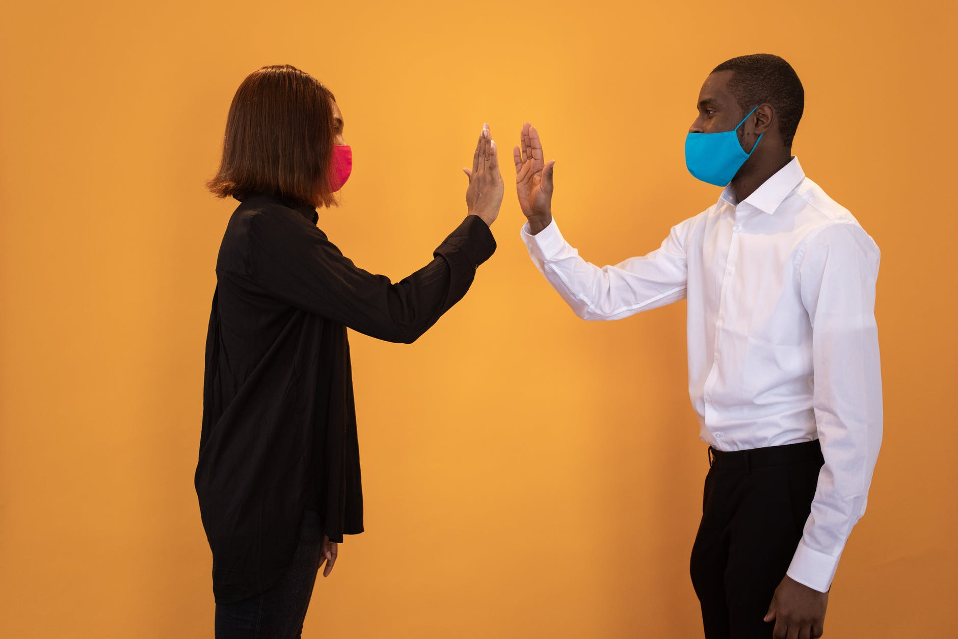 black couple in masks giving high five in studio
