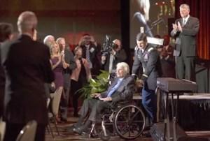 Billy Graham durante su celebración junto a su nieto Will, al fondo su hijo Franklin como anfitrión del evento / BGEA