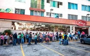 Decenas de personas hacen filas frente a un supermercado para poder comprar alimentos / EFE