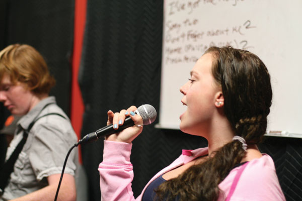Rebecca Segars belts out a long high note during Wednesdays private house band rehearsal at the Palo Alto School of Rock location in Midtown.