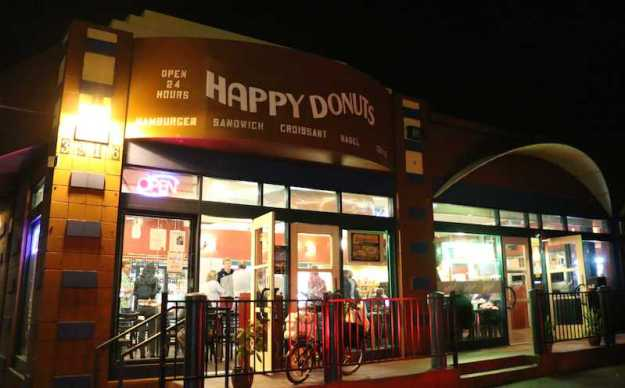 Light floods out of Happy Donuts' iconic exterior as late night customers sit inside.