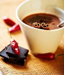 Mug of hot chocolate with cinnamon and chili pepper