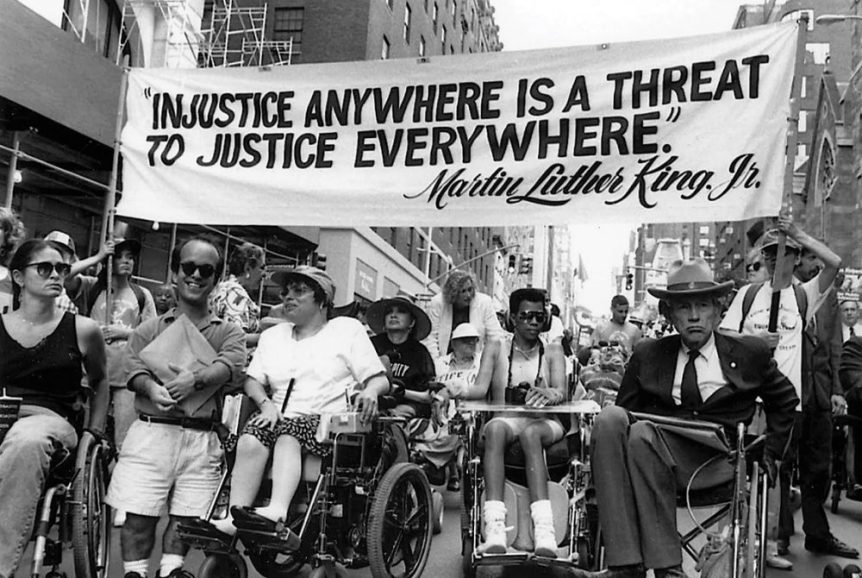 """Image: black and white photograph of individuals in wheelchairs, and with other visible disabilities, taking part in a political march. Participants carry a banner that reads: """"Injustice Anywhere Is a Threat To Justice Everywhere ~ Martin Luther King Jr."""""""