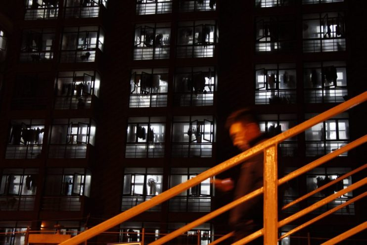 A man walking down a flight of stairs in the city at night looking at his mobile phone