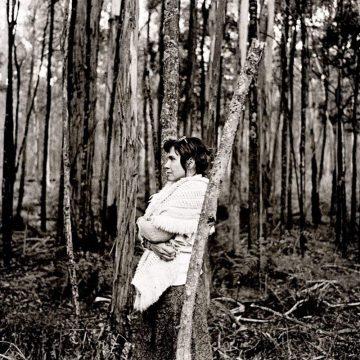 Judith Nangala Crispin leaning on a tree in the Australian bush