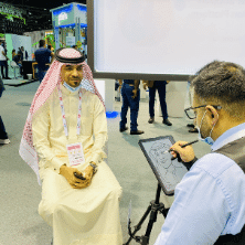Visitor getting a caricature drawn at verloop's stall at GITEX 2020