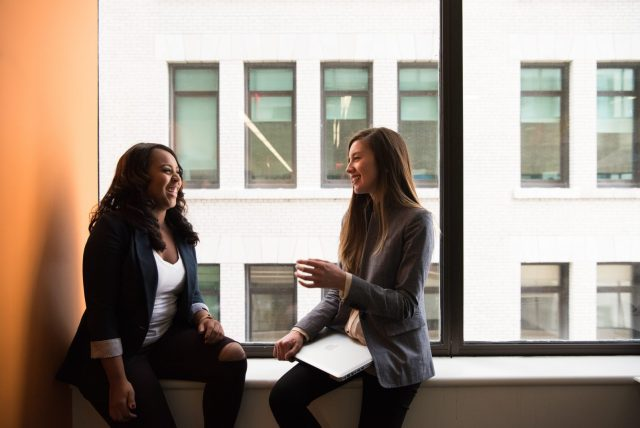 two woman sitting by the window laughing app development small business