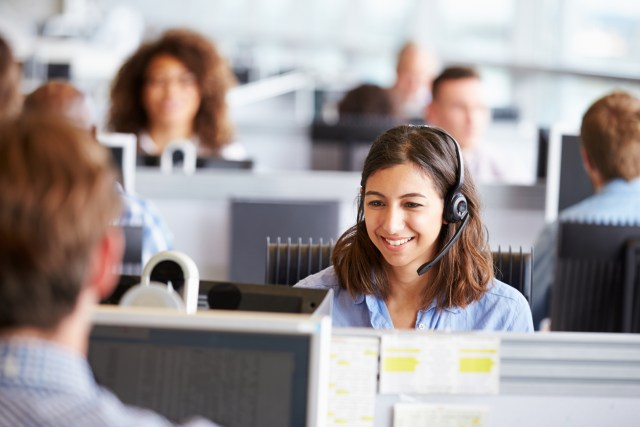 female customer service representative in a call center smiling while surrounded by her coworkers
