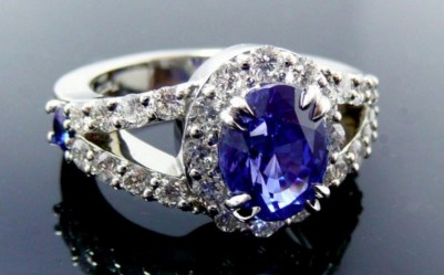 Split shank diamond encrusted platinum engagement ring with a sapphire center stone.