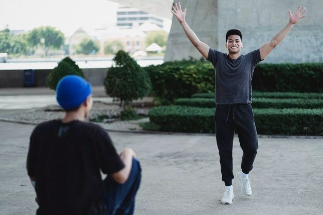 cheerful asian man raising arms in excitement on sunny street