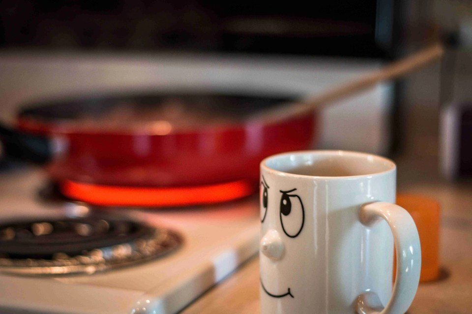 Picture of a coffee cup with a hot pan in the background