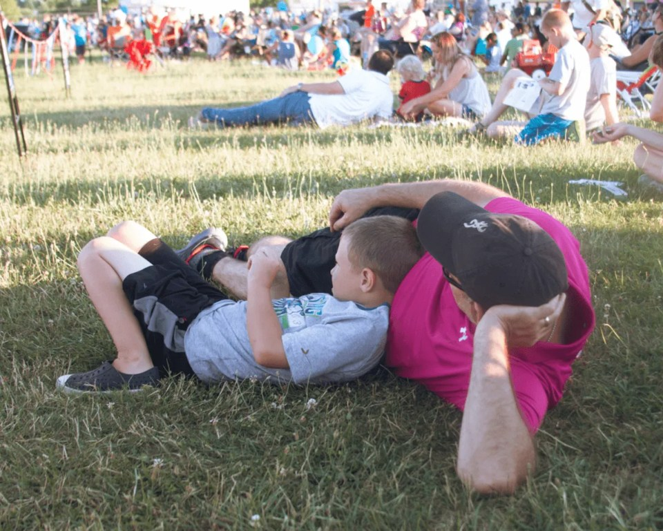 dad and son lying on grass following rules for cropping photos