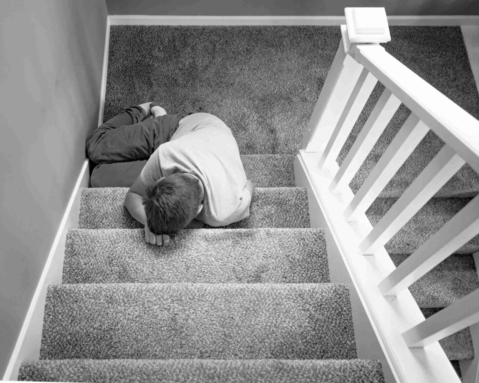 A boy on the stairwell resting his head on the steps