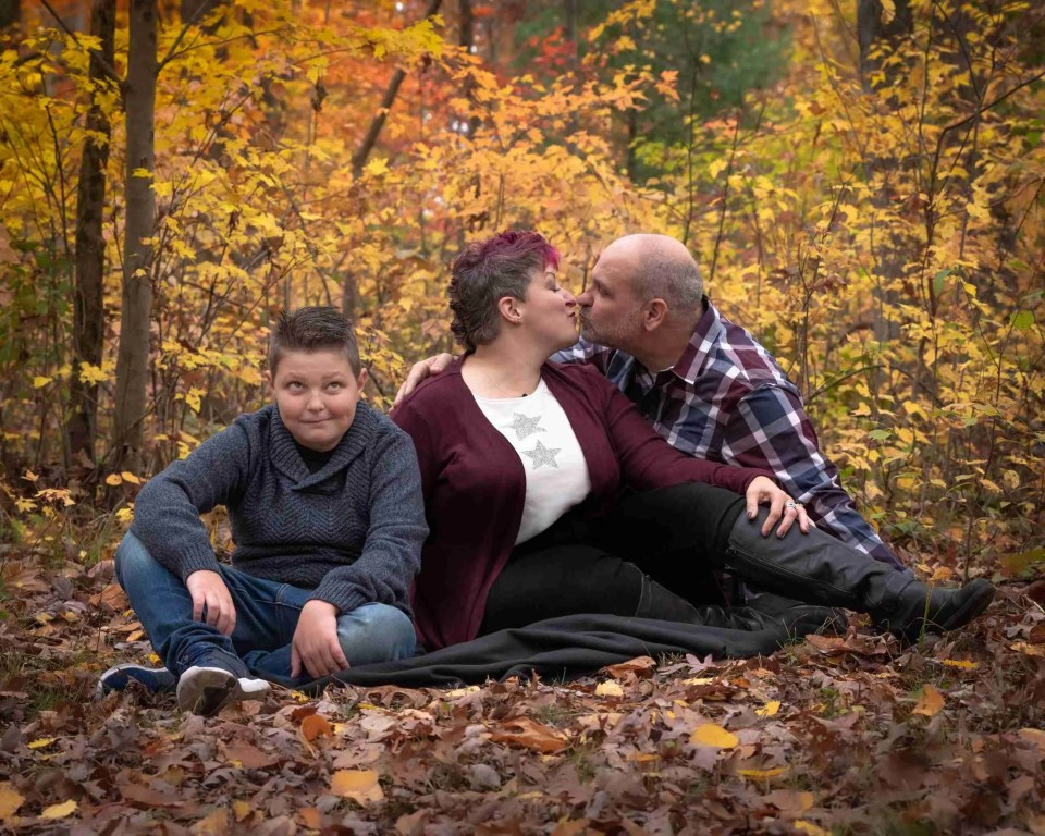 boy rolling his eyes while mom and dad kiss behind him using kisses are gross photography prompt for families