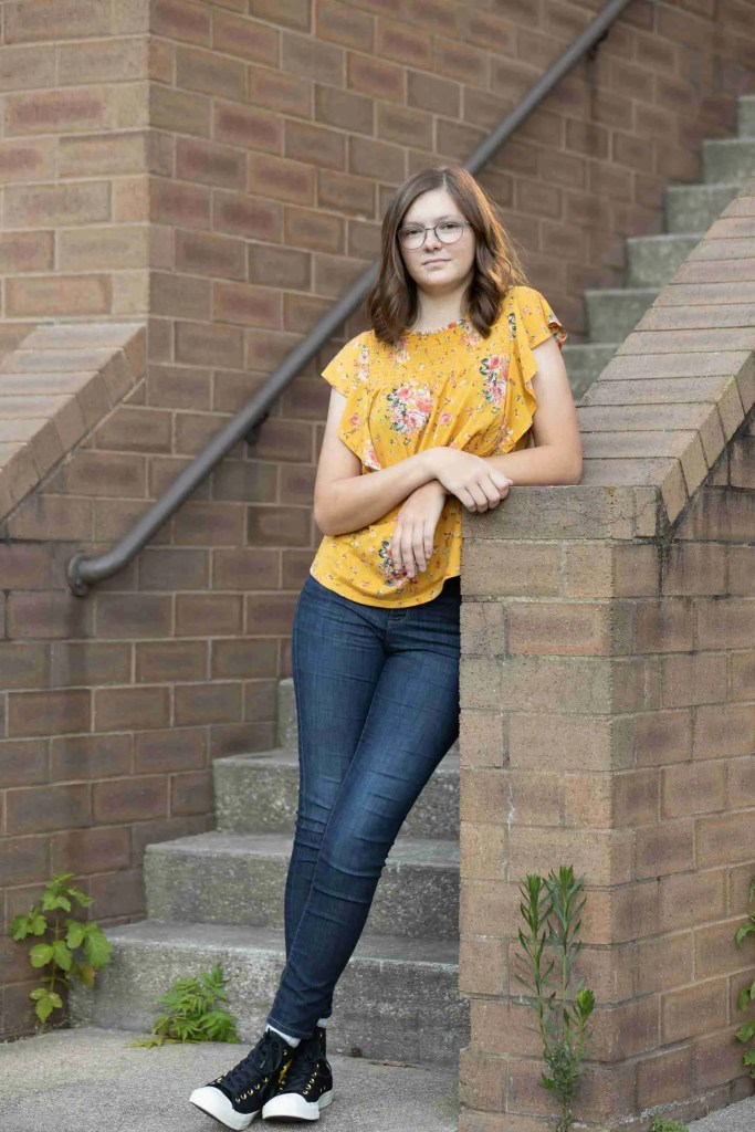 A cute girl pose with a girl in a yellow blouse leaning on a stairwell