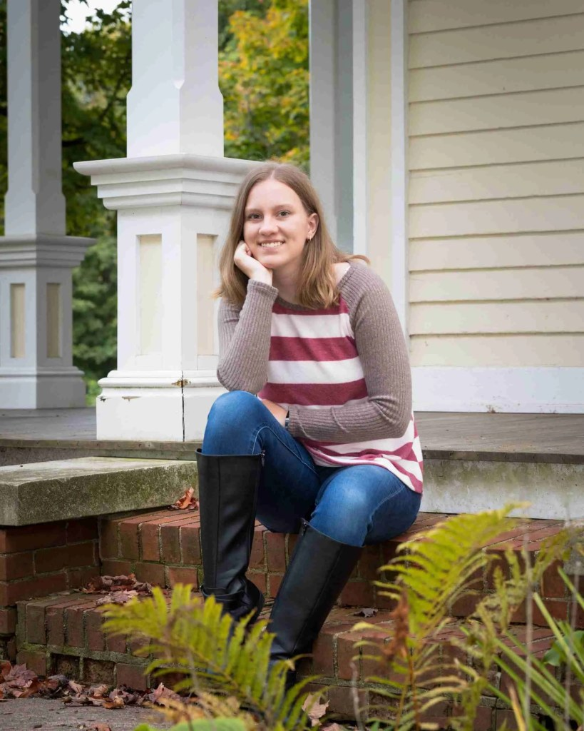 A girl sitting on a stoop with her face resting on her hand