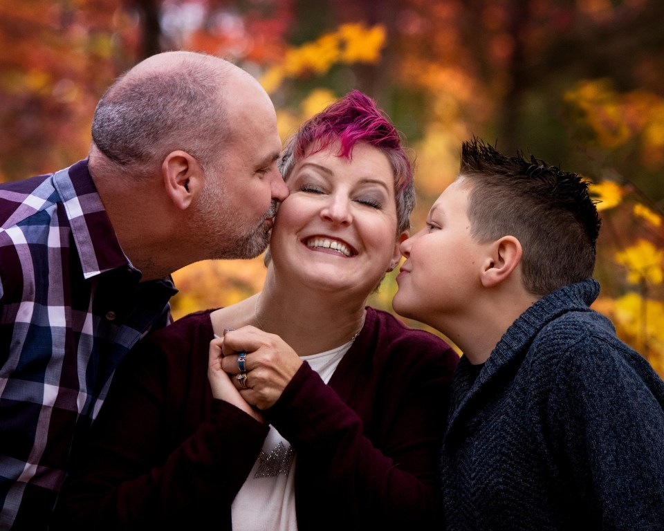 autumn photoshoot with dad and son kissing mom on cheeks