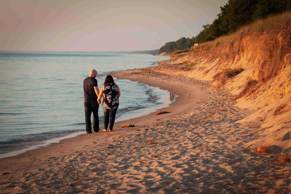 A couple walks down the beach together at Tunnel Park