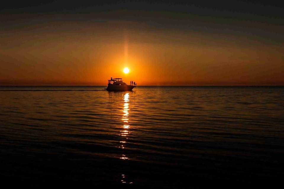 a boat passes in front of a setting sun