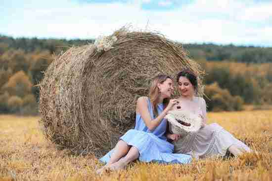 two women connecting in front of a hay bale for an autumn photoshoot