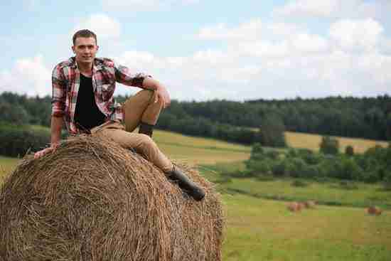 A man on a hay roll for an autumn photoshoot