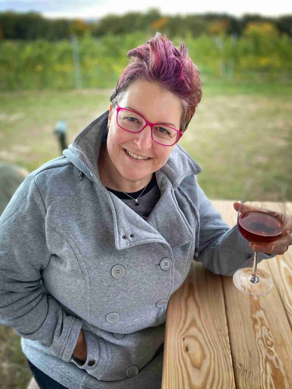 woman with a glass of wine and pink hair