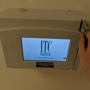 "A small digital box with a screen that says ""swipe to begin"" and a card swipe area on the right hand side"
