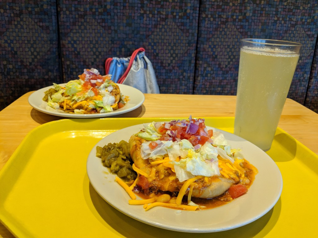 Two plates of Indian tacos with fry bread, chili, lettuce, tomatoes, onions, cheese, and other pepprs with a glass of pineapple agua fresca
